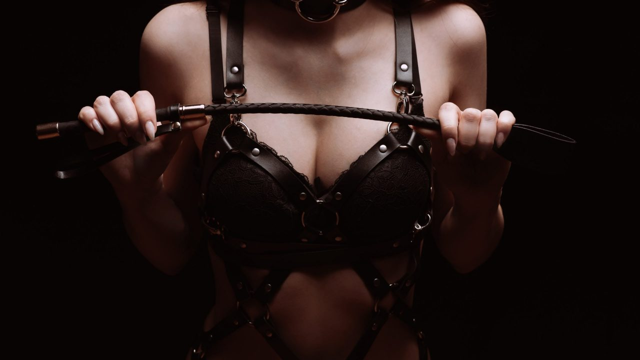 Sexy girl black beautiful bra playing with whip. The concept of BDSM